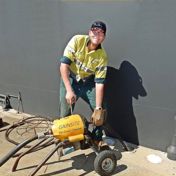 plumber with drain cleaning machine