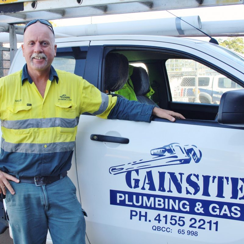 licenced plumber and gas fitter standing next to ute
